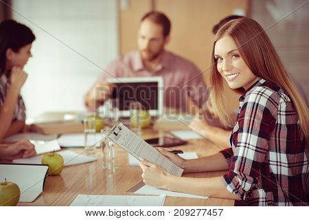 Successful businesswoman. Cheerful beautiful smart woman holding her notes and smiling while attending a business meeting
