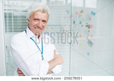 Happy mature detective in white shirt looking at camera in office