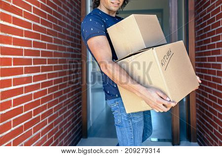 Young man carrying moving in cardboard boxes