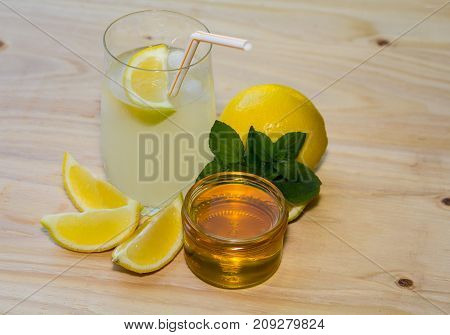 Fresh homemade lemonade in clear glass with lemon slices and a drinking straw, fresh mint and honey in a glass jar and lemon on the side. On a wood background.