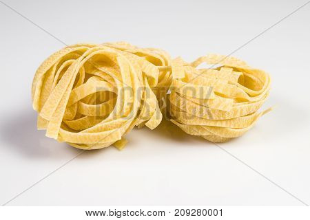 Uncooked and raw tagliatelle isolated on white.