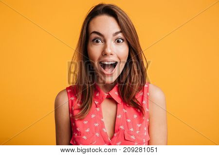 Close up of happy amazed woman with open mouth looking at camera, isolated over yellow background