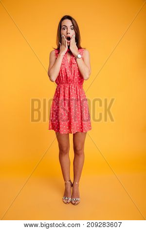 Full length portrait of pretty frightened woman covering her face with hands, looking at camera, isolated on yellow background