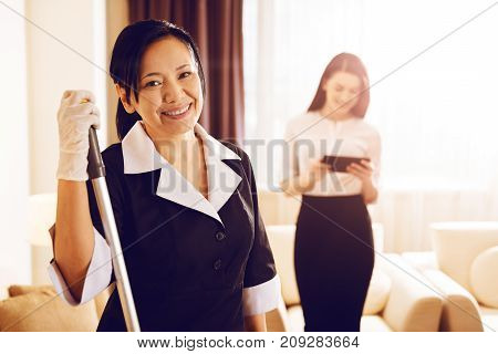 Ready to work. Attractive female keeping smile on her face and holding mop in right hand while looking forward