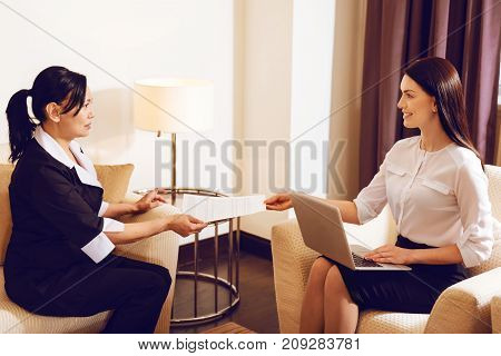 Take it. Confused international female sitting on sofa in semi position and looking at her boss while taking documents