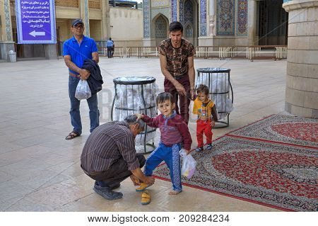 Fars Province Shiraz Iran - 19 april 2017: Shah Cheragh Shrine Fathers help their sons change their shoes after visiting the mosque for prayer.