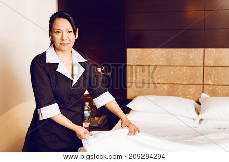 Do it carefully. Cheerful female person making bed while posing on camera and being in special uniform
