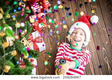 Happy child holding party popper. Funny kid on Christmas eve. Xmas holiday concept