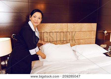During work. Positive room cleaner standing in semi position and keeping smile on face while looking straight at camera