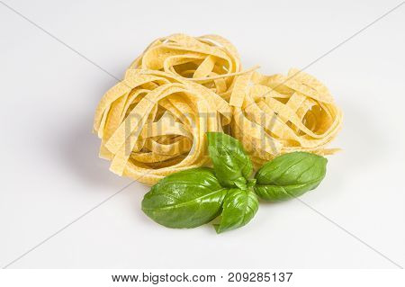 Uncooked and raw tagliatelle with basil leaves isolated on white.