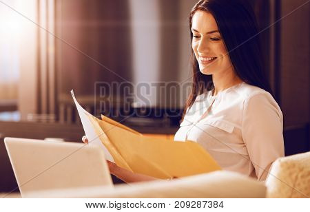 Be positive. Attractive brunette keeping friendly smile on face and looking downwards while sitting in semi position