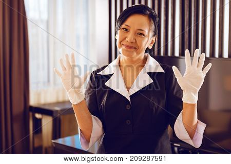 Hands up. Positive delighted international room cleaner keeping smile on her face and being in uniform while looking straight at camera