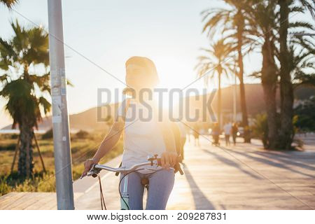 Beautiful sunset sunlight beams light on beautiful stylish teenager in white tshirt and blue denim jeans riding her cruiser commuter city bike on promenade of coastal town