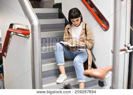 Attractive brunette woman or teenager sits on stairs of double decker train female student studies or prepares for exams on early morning commute