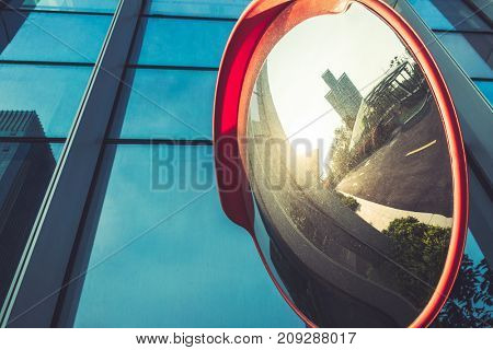road mirror reflection against glass building.