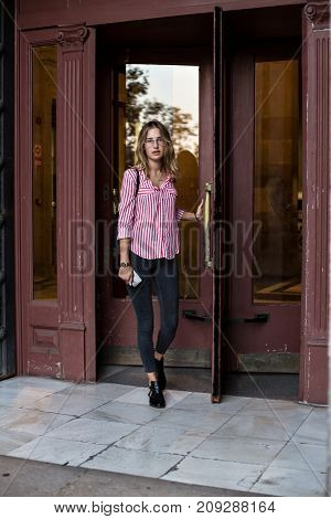 Pretty and cute feminine woman in skinny jeans and red shirt leaves building through vintage wooden rotating doors on warm summer evening on way to business meeting