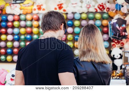 Attractive young hipster couple choose which game to play at county fair carnival popping colorful baloons to win prize on romantic date during summer break