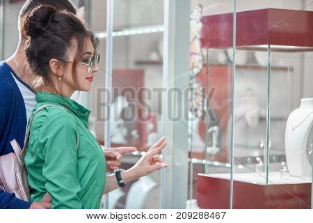 Attractive young woman choosing jewelry at the boutique shopping with her boyfriend.