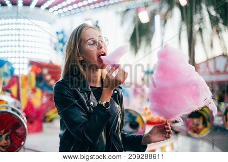 Happy beautiful teenager girl or woman eats with appetite huge cloud of pink cotton candy at festival or fair during carnival in front of amusement park attraction at summer