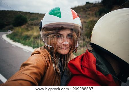 Beautiful woman with long blonde hair sits on passenger back seat of motorcycle wears protection helmet with visor makes selfie close to driver or boyfriend