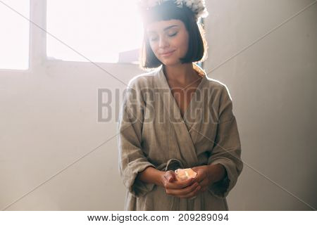 Tender and sensual photo of young natural beautiful woman in cotton linen organic bath robe holding melted wax candle prepares for relaxation or spa at cosy home