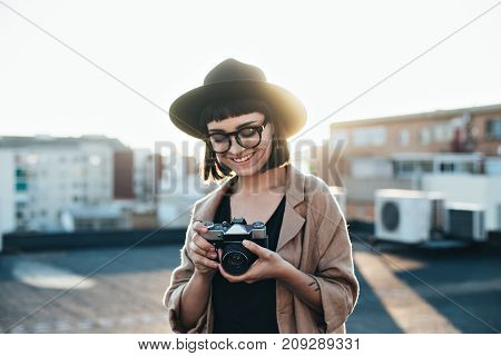 Smiling and laughing young woman professional photographer stands on top of rooftop in city on warm summer evening makes photos with retro vintage analog camera
