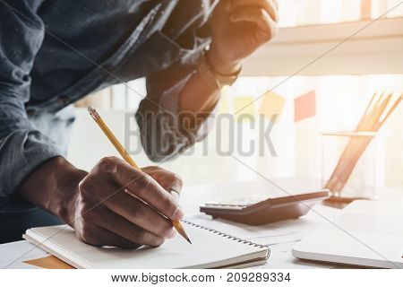 Close Up Accountant Man Using Calculator While Writing Make Note About Cost Profit At Home Office.