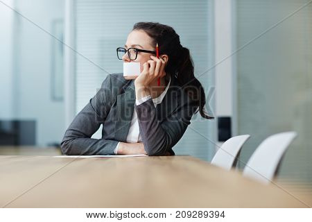 Pensive businesswoman with cellotaped mouth thinking of ideas by desk