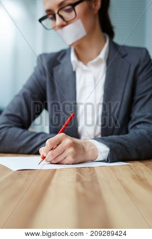 Young female with her mouth shut by cellotape making notes with pencil