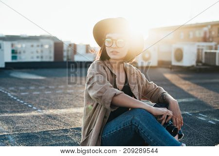 Smiling and laughing young model teenager or woman in hipster outfit glasses and fedora hat holds vintage analog photo camera sits on top of rooftop during summer sunset