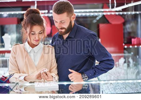 Gorgeous young woman and her handsome boyfriend looking at the glass display choosing engagement rings at the jewelry store.