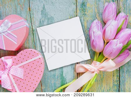 Bouquet of pink tulips tied with a satin ribbon two pink gift boxes in the shape of heart with a bow and white blank paper card are on the old blue wooden background with space for text