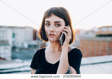 Sensitive and sensual cute pretty woman or teenager looks in camera talks on smartphone in amazing sunset light leaks adorable and nice smiles gently