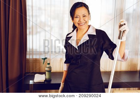 Friendly atmosphere. Beautiful brunette keeping smile on her face and wearing uniform while leaning on swab