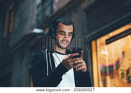 Handsome young man in black hoodie wears big wireless music headphones and changes audio tracks on smartphone he smiles when looks at phone screen
