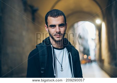 Handsome attractive young man or teenager stands in middle of street in old town looks straight at camera serious but slightly smiling in cool and millennial manner