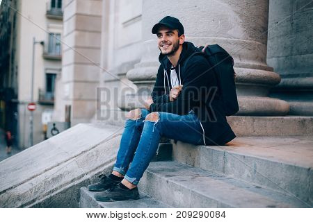 Smiling happy teenager or young hipster student sits on top of stairs in front of university or highschool wears black hoodie and cap smiles at camera successful and handsome