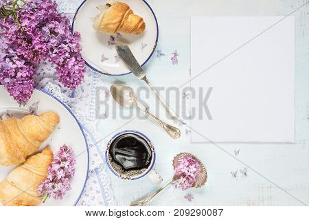 Spring breakfast with a cup of black coffee croissants white blank paper card and lilac flowers with space for text