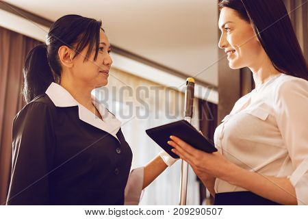 My helper. Positive delighted woman holding her gadget and feeling happiness while looking at hotel staff