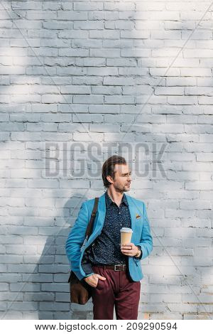 handsome businessman holding paper cup and looking away outside