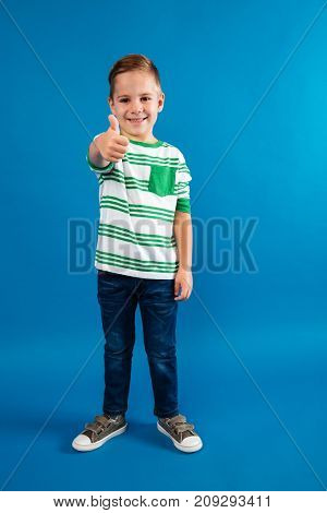 Full length portrait of a funny young kid standing and showing thumbs up gesture isolated over blue background