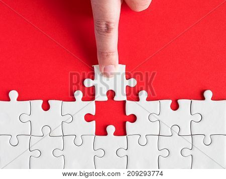 Woman use finger to fill white jigsaw puzzle on red background in top view (Business Concept)