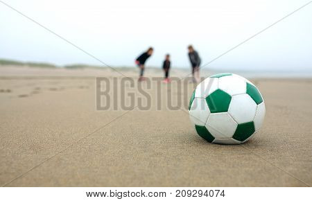 Close up of soccer ball with three people in the background