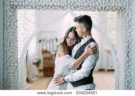 Cheerful young bride smiling and hugging groom while he kisses her in the head and embraces her waist. Beautiful newlyweds posing in vintage room. Close-up