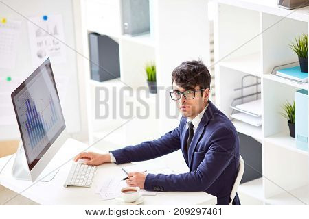 Serious stock-broker sitting by workplace in front of computer monitor
