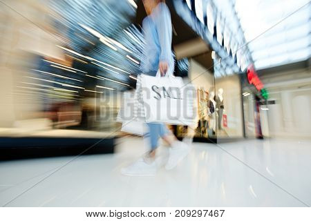 Hurrying shopper with paperbags moving along display windows on black friday