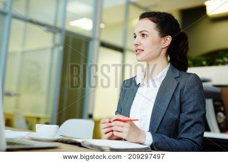 Pensive young woman brainstorming while preparing report for seminar