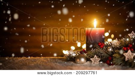 Burning candle Christmas decoration and wooden background in falling snow elegant low-key shot with festive mood