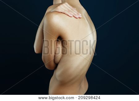 Beautiful well-groomed body of a woman on dark background