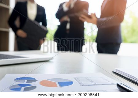 Business Document In Touchpad Lying On The Desk, Office Workers Discussting Meeting In The Backgroun